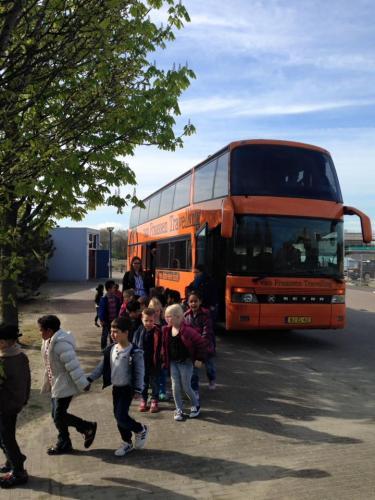 Kinderen komen per bus naar het theater.